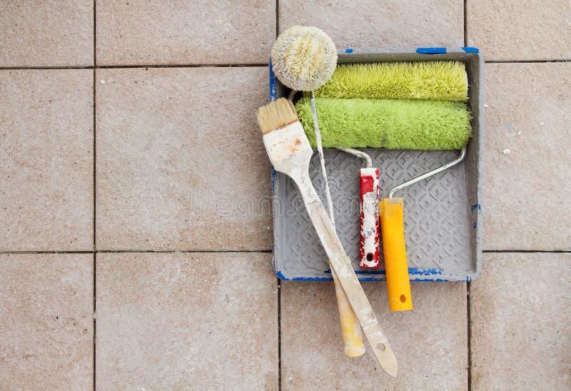 Ripari gli strumenti sopra il fondo di pietra della piastrella per pavimento. Copi lo spazio. immagini stock