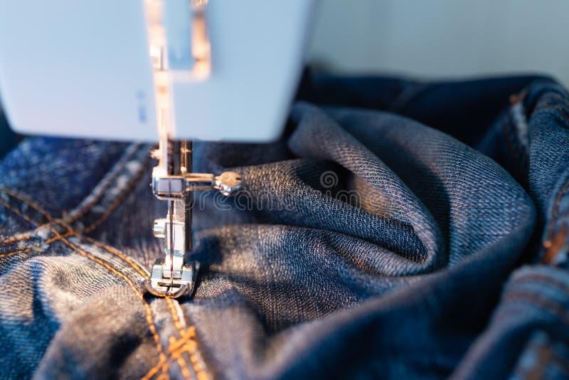 Ripari i jeans sulla macchina per cucire Vista del tessuto, dell'ago e del filo Illuminazione dalla lampada incandescente incorpo immagine stock