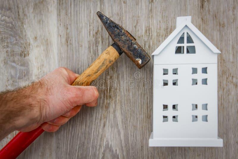Ripari il concetto della casa martello a disposizione del costruttore e del Mo miniatura immagini stock