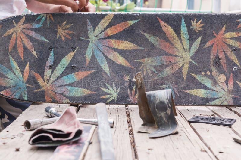 Ripari il vecchio bordo del pattino su una tavola di legno nel giardino sui precedenti dei bulloni, della carta vetrata e di una  fotografia stock libera da diritti