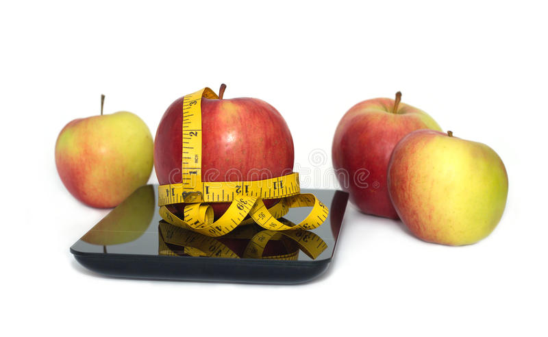 Ripe apple, kitchen scales and measuring tape isolated closeup royalty free stock photography
