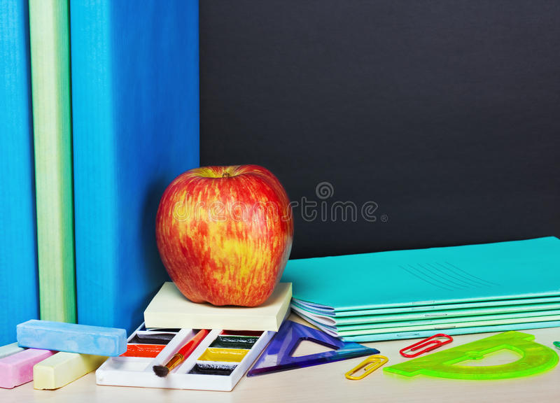 Ripe apple and school supplies