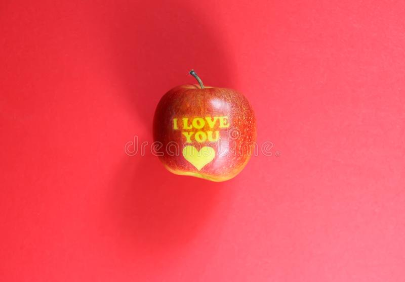Apple with words I LOVE YOU on red background stock image