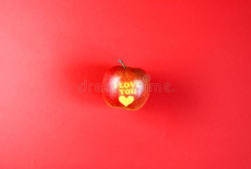Apple with words I LOVE YOU on red background royalty free stock photo