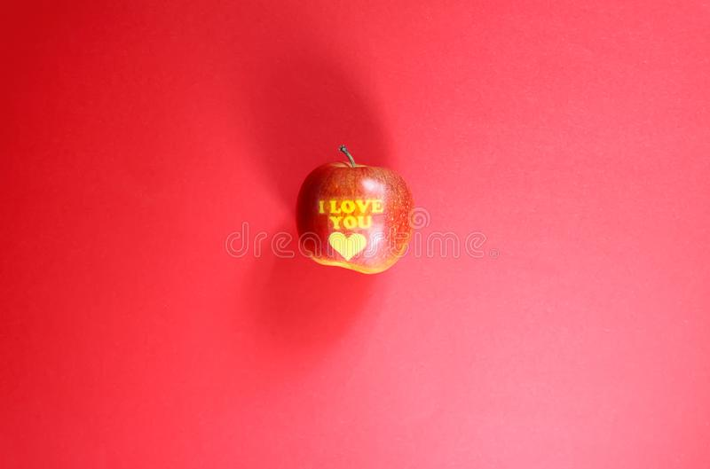 Apple with words I LOVE YOU on red background stock photos