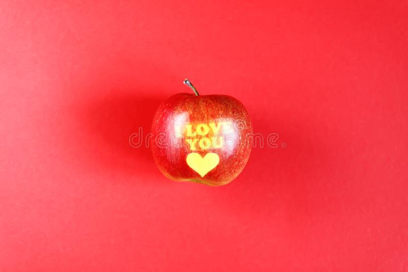 Apple with words I LOVE YOU on red background stock images