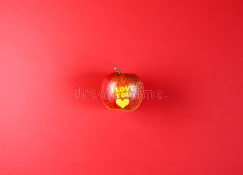 Apple with words I LOVE YOU on red background stock photo