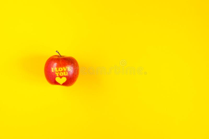 Ripe apple with words I LOVE YOU on yellow background. Ripe apple with words I LOVE YOU on bright yellow background stock photos