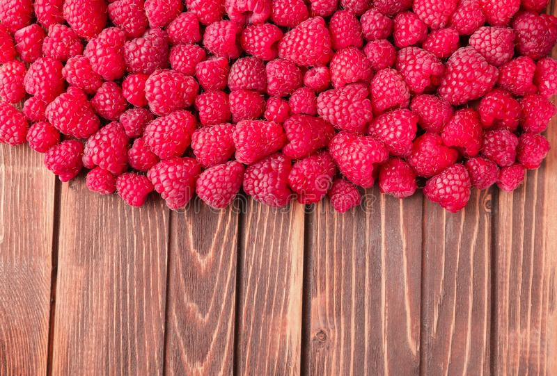 Ripe aromatic raspberries on wooden background stock photos