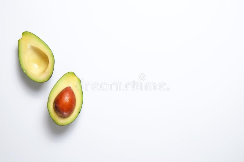 Ripe avocado fruit. Healthy dieting superfood containing good fat. Minimal composition with halved nutrient dense avocado fruit slices full of heart healthy royalty free stock photo