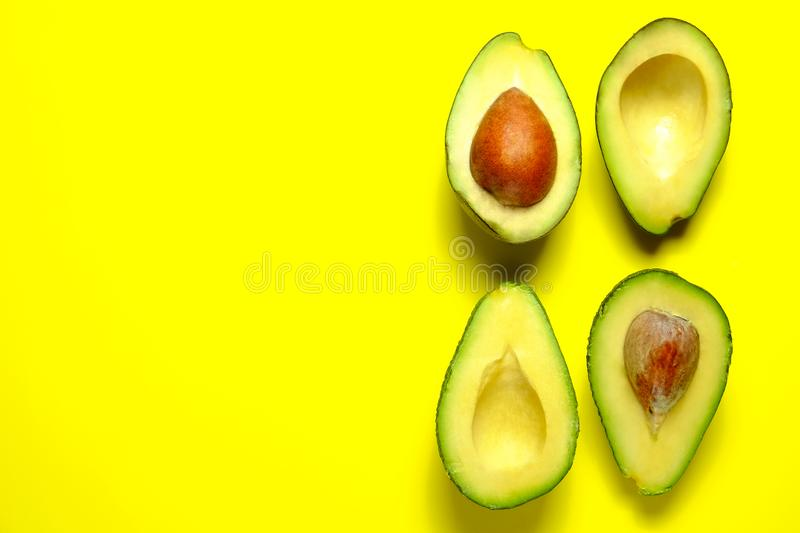 Ripe avocado fruit. Healthy dieting superfood containing good fat. Minimal composition with halved nutrient dense avocado fruit slices full of heart healthy royalty free stock images
