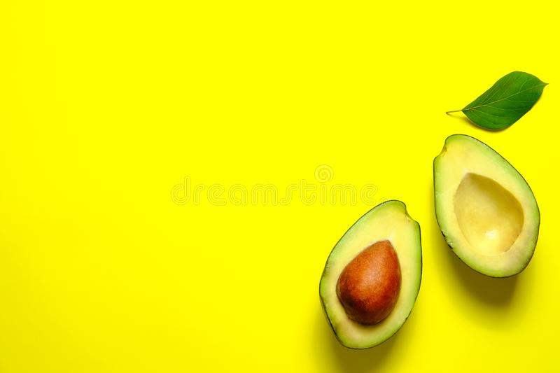 Ripe avocado fruit. Healthy dieting superfood containing good fat. Minimal composition with leaf and halved nutrient dense avocado fruit slices full of heart royalty free stock photo