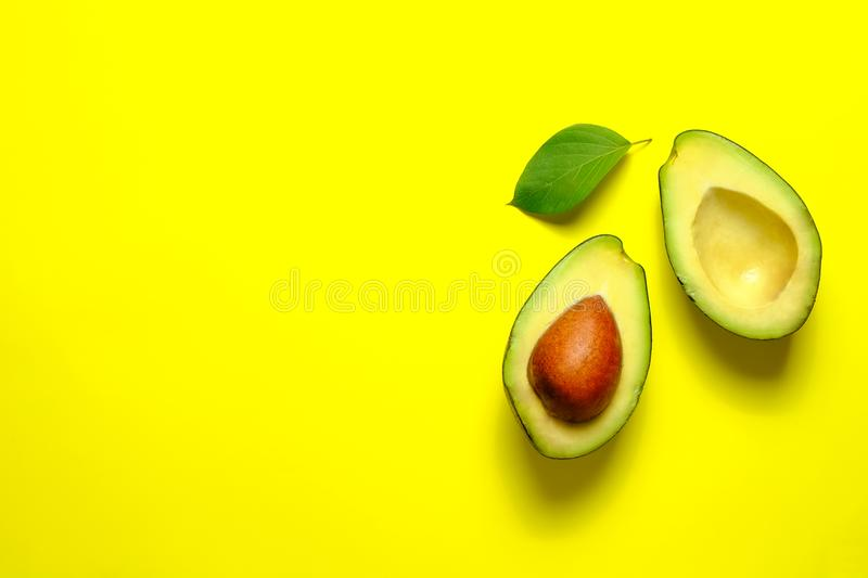 Ripe avocado fruit. Healthy dieting superfood containing good fat. Minimal composition with leaf and halved nutrient dense avocado fruit slices full of heart stock photos