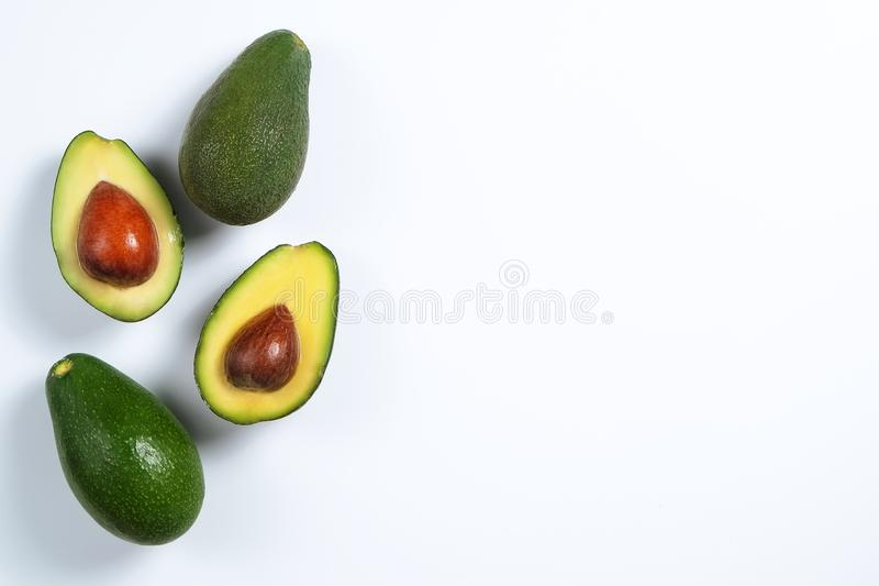 Ripe avocado fruit. Healthy dieting superfood containing good fat. Minimal composition with whole and halved nutrient dense avocado fruit slices full of heart royalty free stock image