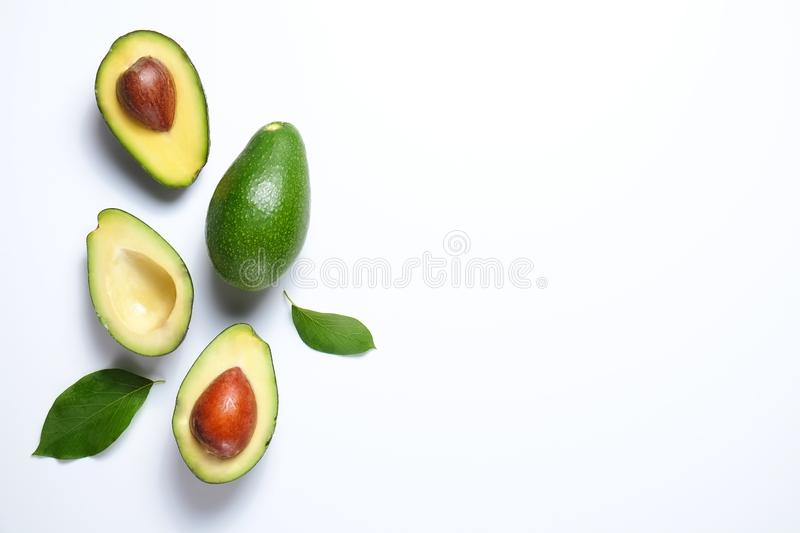 Ripe avocado fruit. Healthy dieting superfood containing good fat. Minimal composition with whole and halved nutrient dense avocado fruit slices full of heart royalty free stock photo