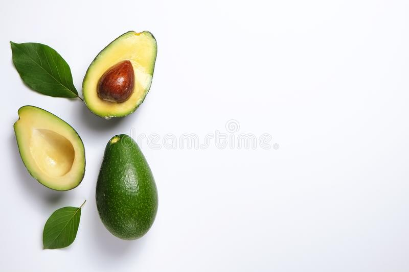 Ripe avocado fruit. Healthy dieting superfood containing good fat. Minimal composition with whole and halved nutrient dense avocado fruit slices full of heart stock photography