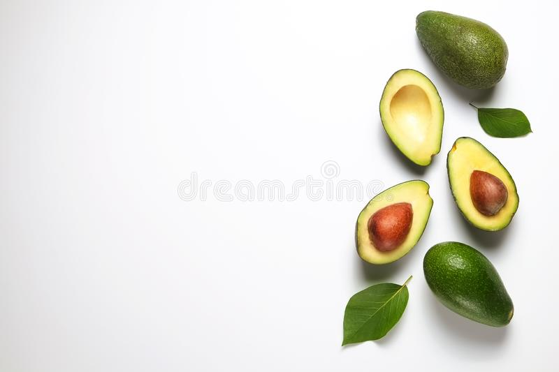 Ripe avocado fruit. Healthy dieting superfood containing good fat. Minimal composition with whole and halved nutrient dense avocado fruit slices full of heart royalty free stock photos