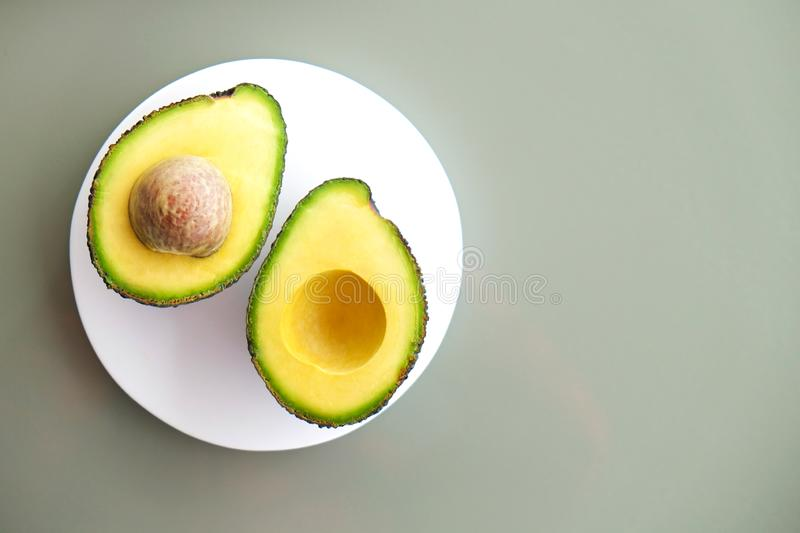 Ripe avocado fruit. Healthy dieting superfood containing good fat. White marble coaster with halved nutrient dense avocado fruit slices full of heart healthy stock photos