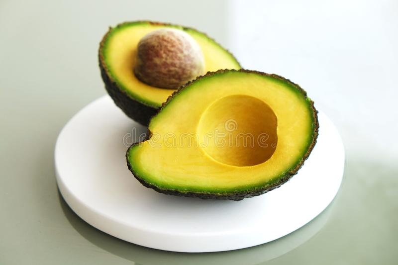 Ripe avocado fruit. Healthy dieting superfood containing good fat. White marble coaster with halved nutrient dense avocado fruit slices full of heart healthy stock images