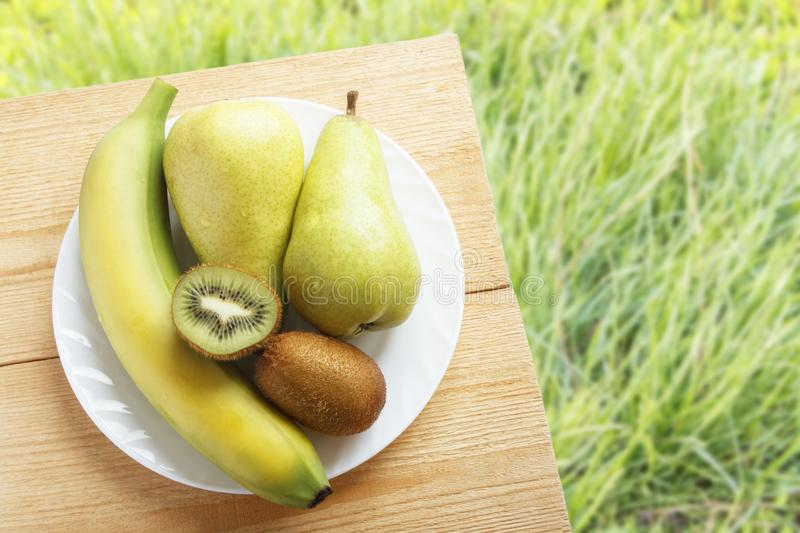 Ripe banana, kiwi fruit and pear on wooden table on background of green grasses. Rustic lifestyle concept. Top view. Copy space.  royalty free stock photography