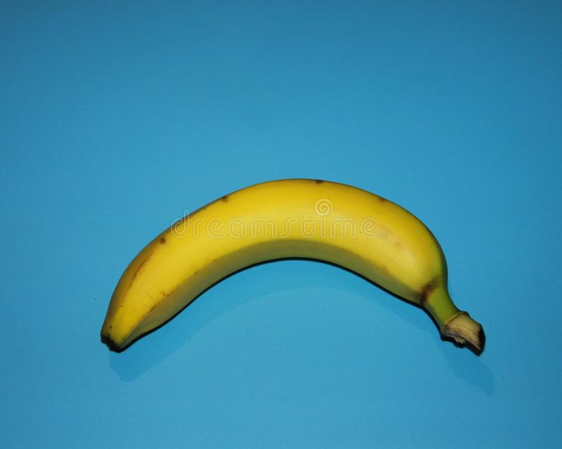 Ripe banana lies on a blue background royalty free stock photo