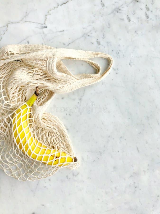 Ripe Banana in una borsa a maglia bianca immagini stock