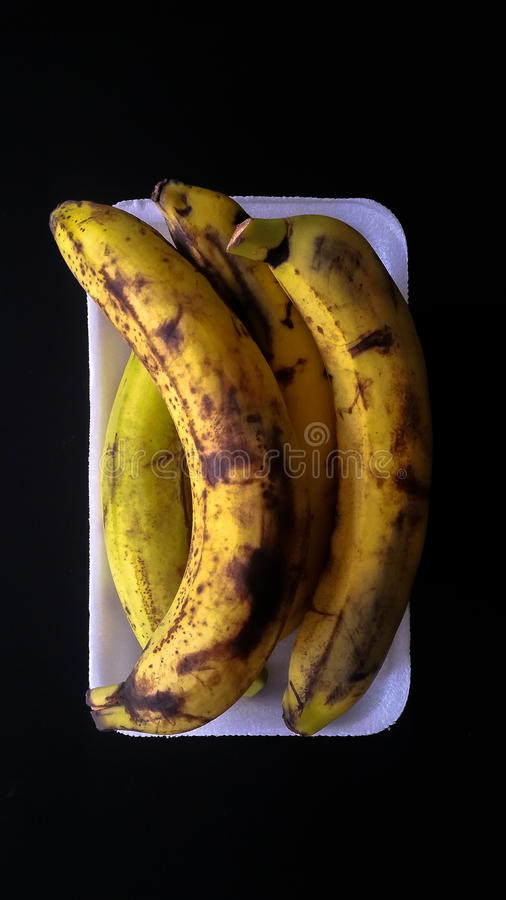 Ripe bananas in a white plate on a black background. Ripe bananas in a white plate stock images