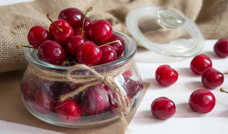 Ripe berries of sweet cherry in a glass jar on a light background stock images