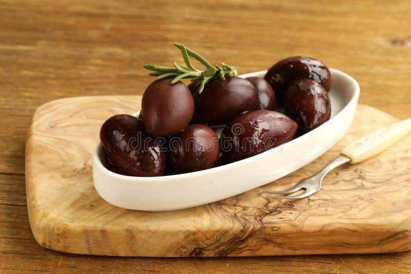 Ripe black kalamata olives. In a white bowl royalty free stock images