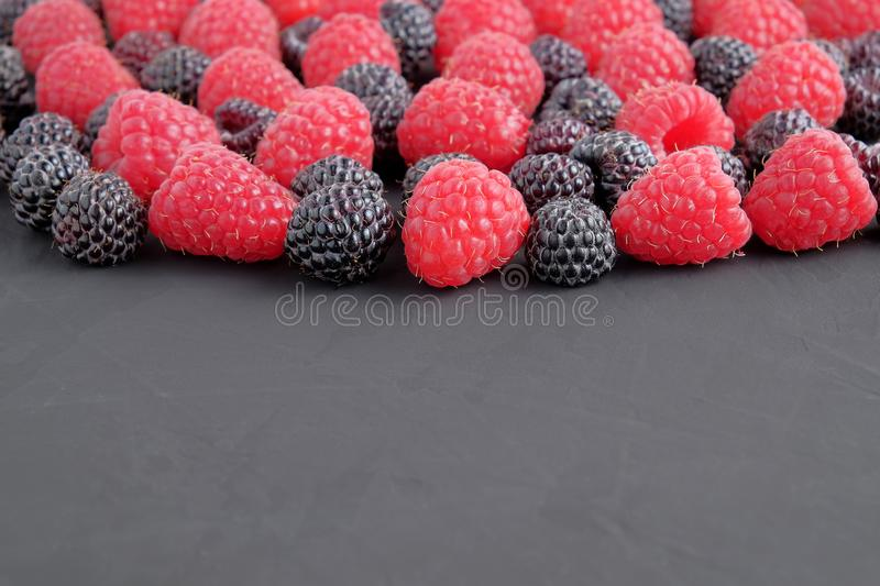 Ripe and black natural raspberries on dark background. Close-up view. stock image