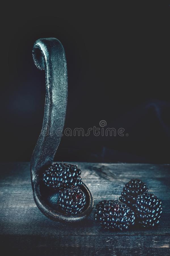 Ripe blackberries in a pot with a clay handle on a wooden background. Art, low key. Copy space royalty free stock photo