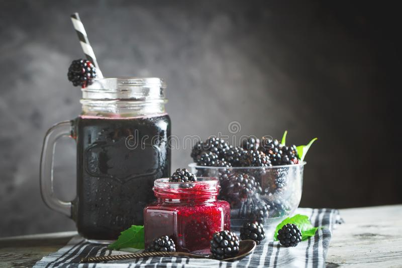 Ripe blackberry, blackberry juice and jam on a wooden table. Dark background. stock photos
