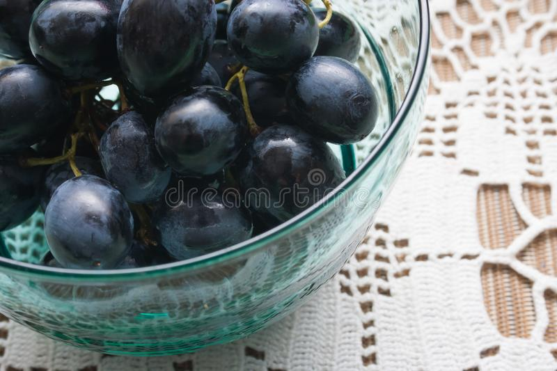 Ripe blue grapes fruits on a table on a white tablecloth stock photo