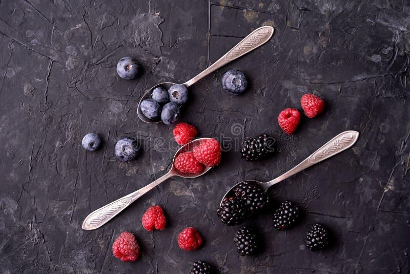 Ripe blueberries, raspberries, blackberries, Mixed berries with three spoons. Various fresh summer berries on dark solid backgroun royalty free stock photo