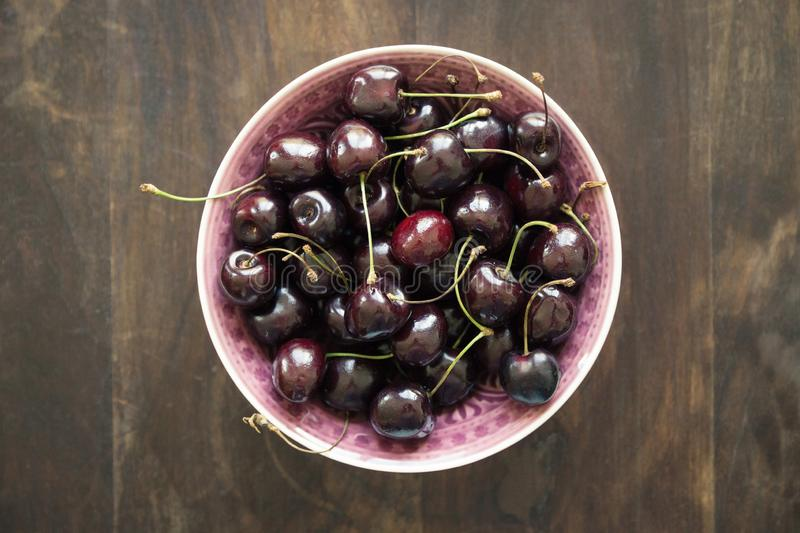 Ripe cherries in a rustic bowl on a wooden plate or table. Flat lay and top view food concept stock images