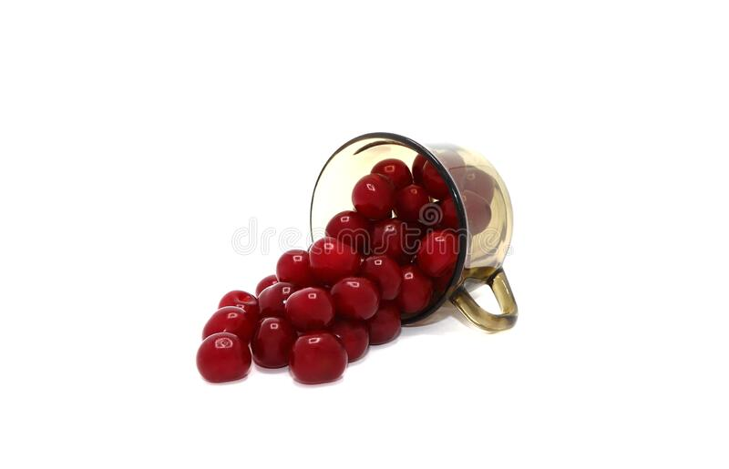 Ripe cherries spilled out of a glass on a light background. stock photos