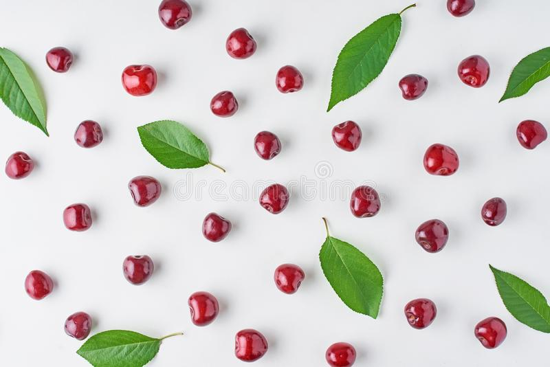 Ripe cherry berries and cherry leaves on a white background, top view flat lay royalty free stock photography