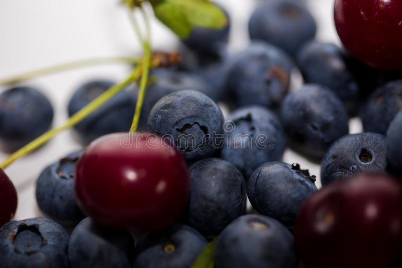Ripe cherry with blueberries on a white background. Closeup of berries with selective focus royalty free stock image