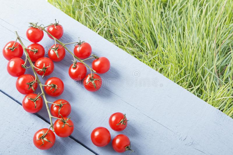 Ripe cherry tomato branch on wooden table in outdoor. Top view. Background of green grasses for copy space.  royalty free stock photography