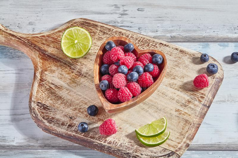 Wooden heart-shaped bowl with ripe sweet raspberries, blueberries and slices of lime on wooden background stock image