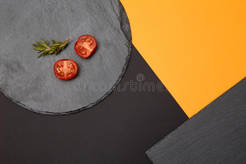 Ripe cherry tomatoes and rosemary composed on black slate boards on colorful background royalty free stock images
