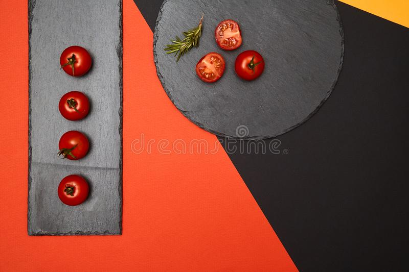 Ripe cherry tomatoes and rosemary composed on black slate boards on colorful background stock photography