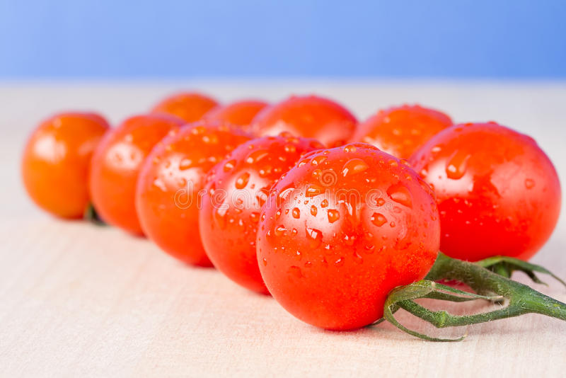 Ripe cherry vine tomatoes on a table. With blue sky background royalty free stock photos