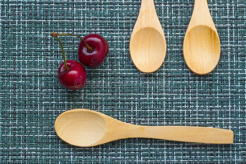 Ripe cherry on a wicker background and three wooden spoons, close-up royalty free stock image