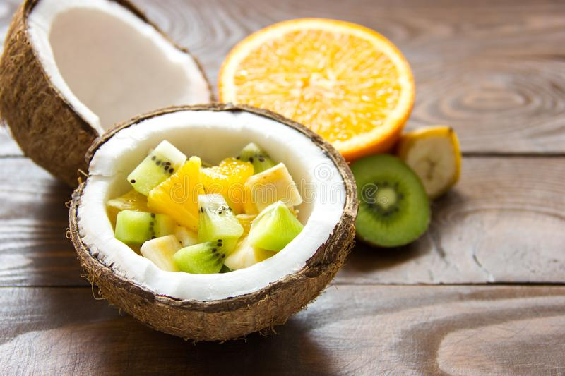 Ripe coconut cracked in half in half coconut fruit salad with orange slices of banana and kiwi fruit stock photos