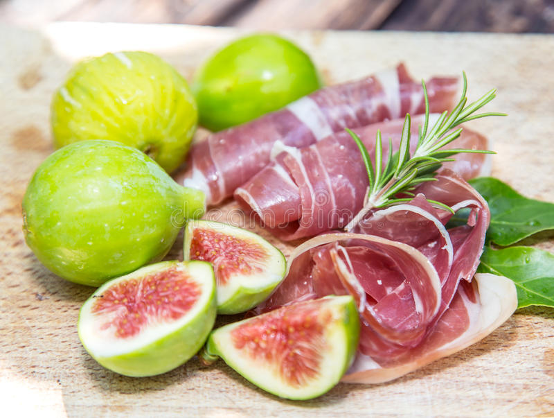 Ripe fig fruits and bacon or prosciutto. Food to accompany the d stock photography
