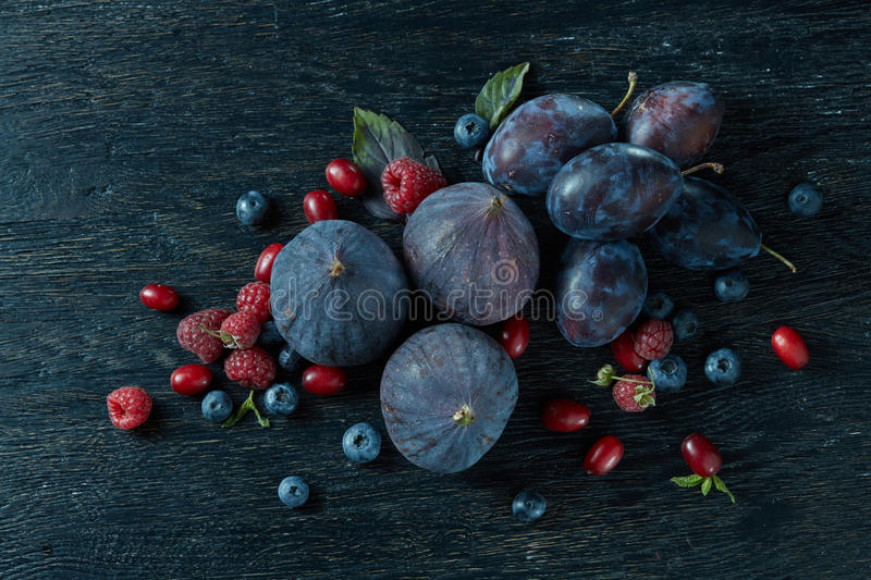 Ripe figs and berries with a bunch of basil royalty free stock photography