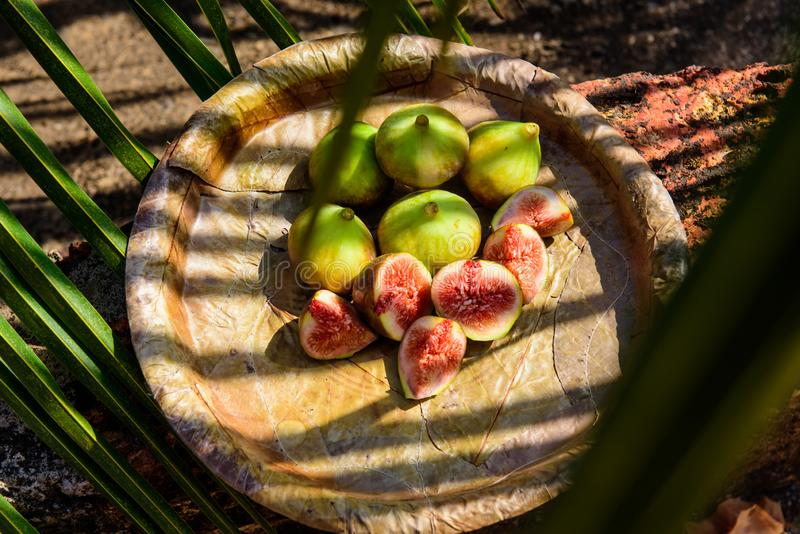 Ripe figs on a plate from leaves close up. Fresh tropical fruits: sweet sliced figs stock images