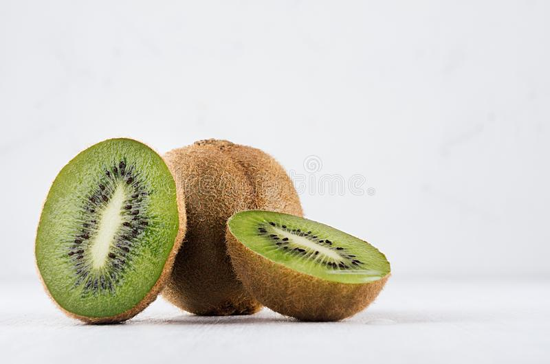 Ripe fleshy green kiwi group with juicy slices on soft light white table. stock photography