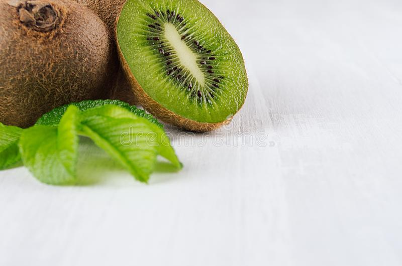 Ripe fleshy green kiwi with juicy slice, young leaves on soft light white table, closeup, top view. Tropical fruits background royalty free stock image